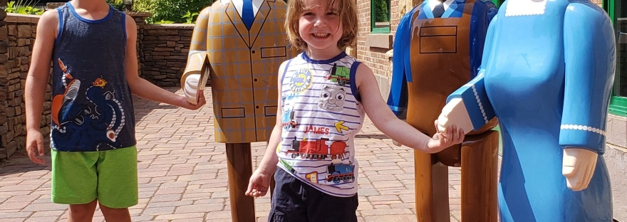 Boys with the Thomas Land people statues